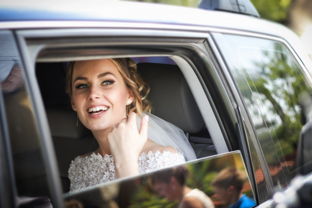 A happy looking bride in a car - Spring bride